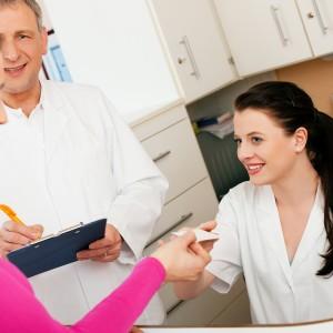 Frau am Empfang einer Arztpraxis